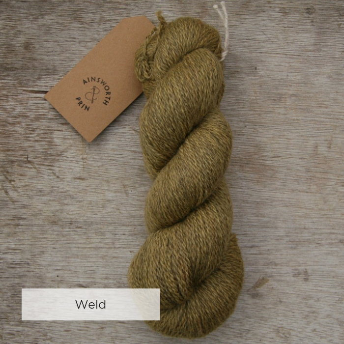 A single skein of soft yellow yarn where the flecks of natural brown show through with a brown tie tag