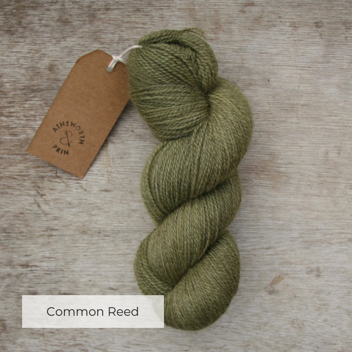 A single skein of soft sage green yarn where the flecks of natural brown show through with a brown tie tag