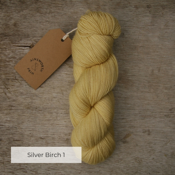 A single skein of soft yellow yarn with a brown tie tag