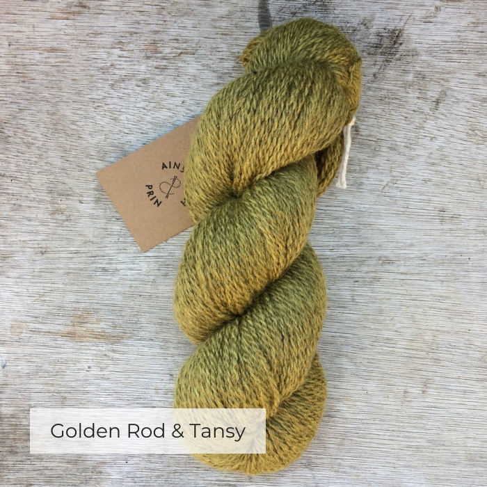 A single skein of naturally dyed yarn in a yellow green colour