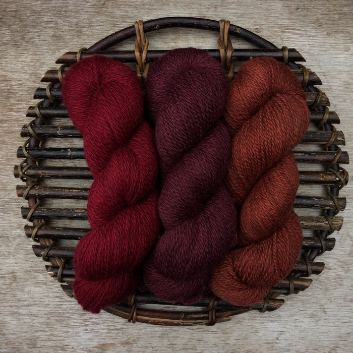 Three skeins of naturally dyed wool in autumnal shades of red, plum and rust lying on a dark, willow platter on a wooden background