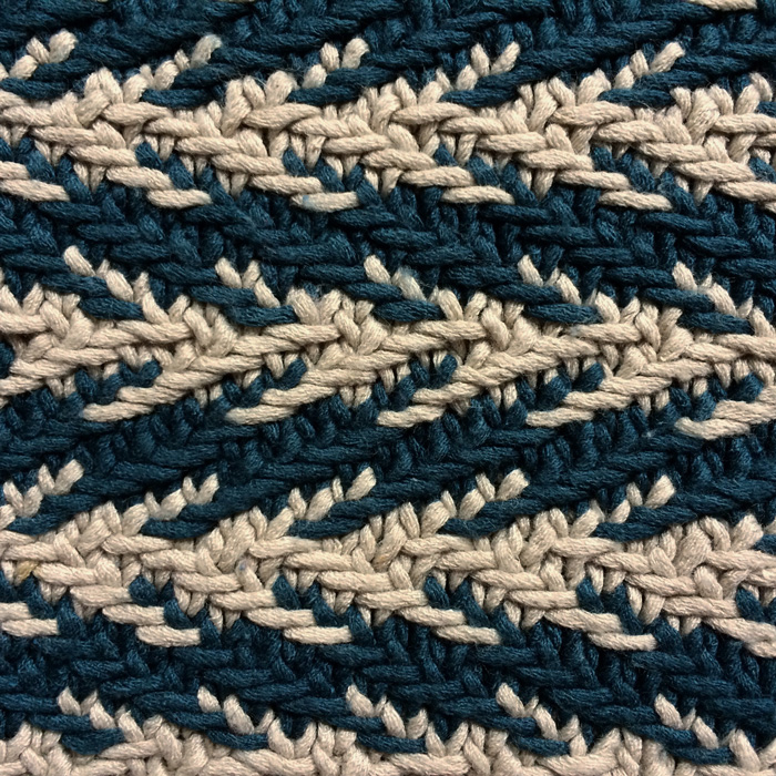 A close up of a knitted herringbone swatch in teal and off white