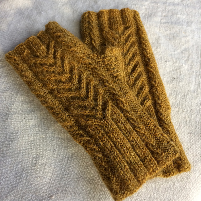 A pair of mustard yellow fingerless, cabled gloves laying on a white linen background