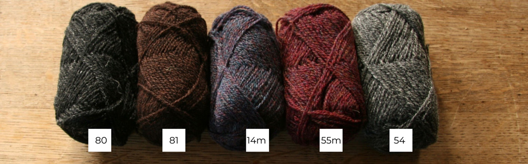 Five balls of Shetland wool lined up in a row from light to dark