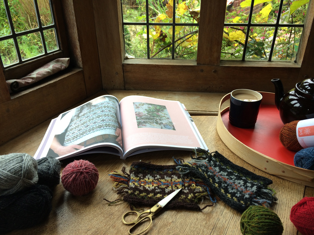 A table in front of a leaded bay window. An open pattern book is surrounded by balls of Shetland wool and knitted colour work samples. There is a tray with a mug of tea and a teapot.