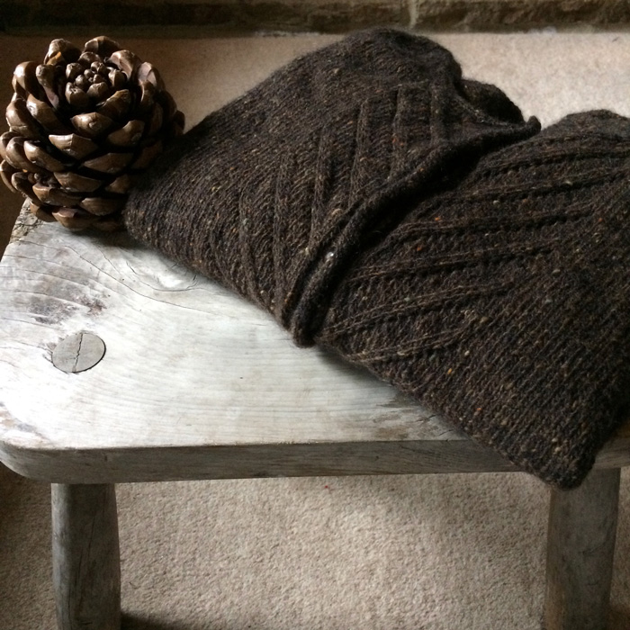 A brown tweedy cardigan folded neatly on a wooden stool with a large pinecone