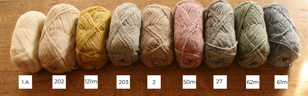 Nine balls of Shetland wool lined up in a row from light to dark