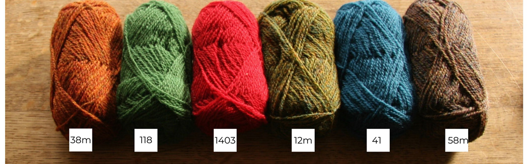 Six balls of Shetland wool lined up in a row from light to dark