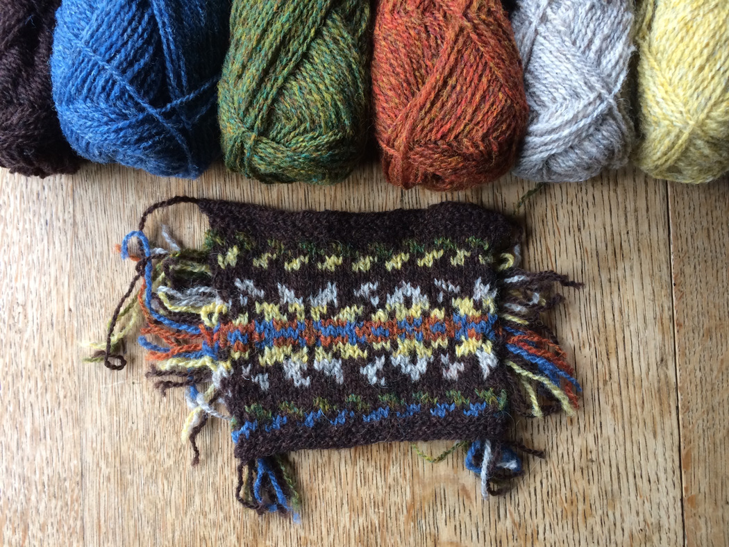 A swatch of knitted colour work with the responding coloured wool above them