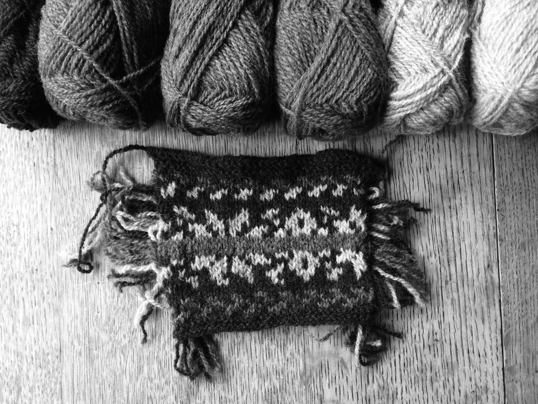 A swatch of knitted colour work with the responding coloured wool above them in black and white