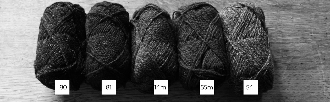 Five balls of Shetland wool lined up in a row from light to dark in black and white