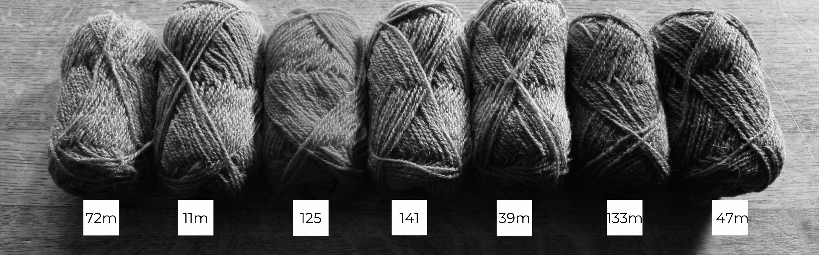 Seven balls of Shetland wool lined up in a row from light to dark in black and white