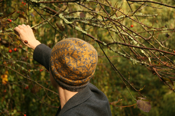 A woman standing in front of a bush and reaching up for some berries and wearing a slouchy mustard and grey beanie with an arrow design