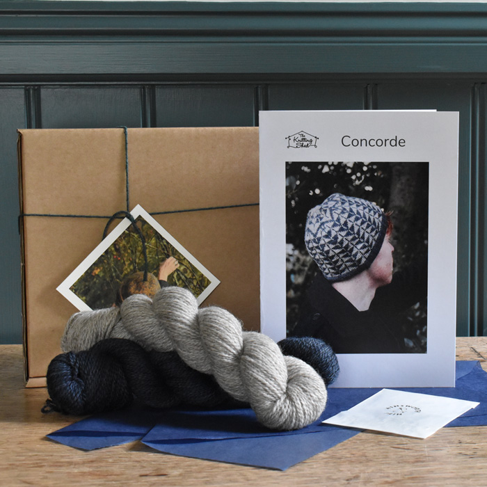 Kit contents: two skeins of BFL & Masham yarn in deep blue and natural laying on blue tissue paper in front of a cardboard box and printed pattern