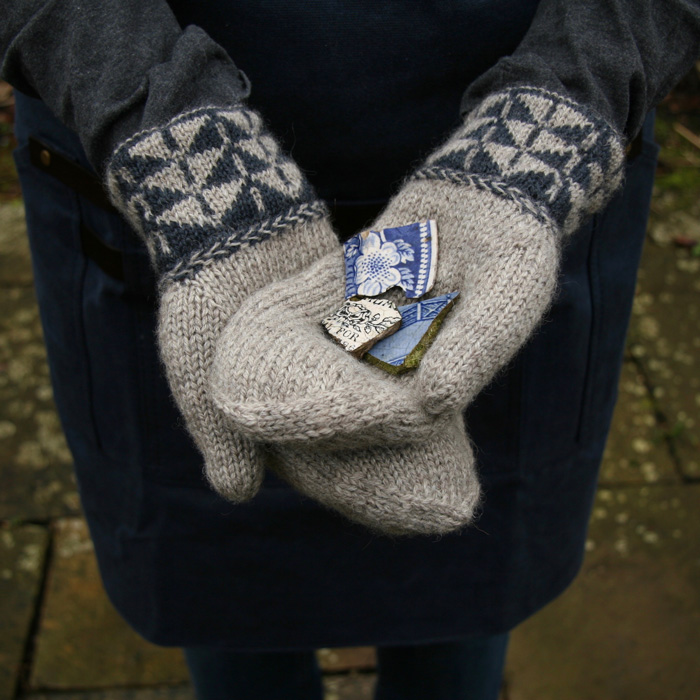 The hands of a woman crossed together with the palms upwards wearing a pair of mittens with colour work cuffs and Latvian braid and holding shards of blue and white pottery