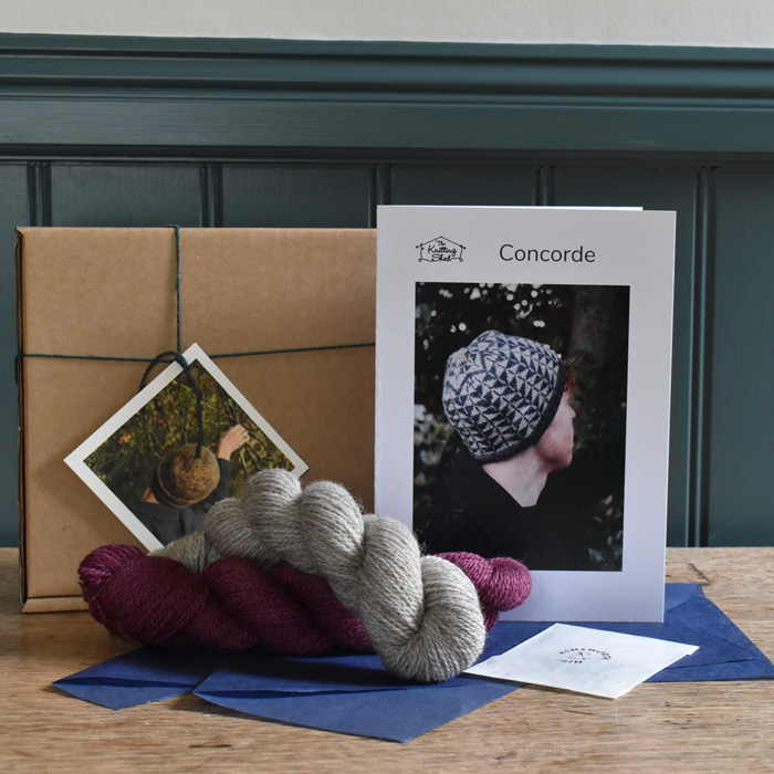 Kit contents: two skeins of BFL & Masham yarn in deep red and natural laying on blue tissue paper in front of a cardboard box and printed pattern