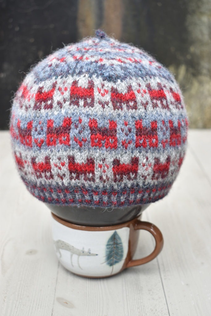 Fairisle knitted hat blocking on a balloon, supported by a teacup