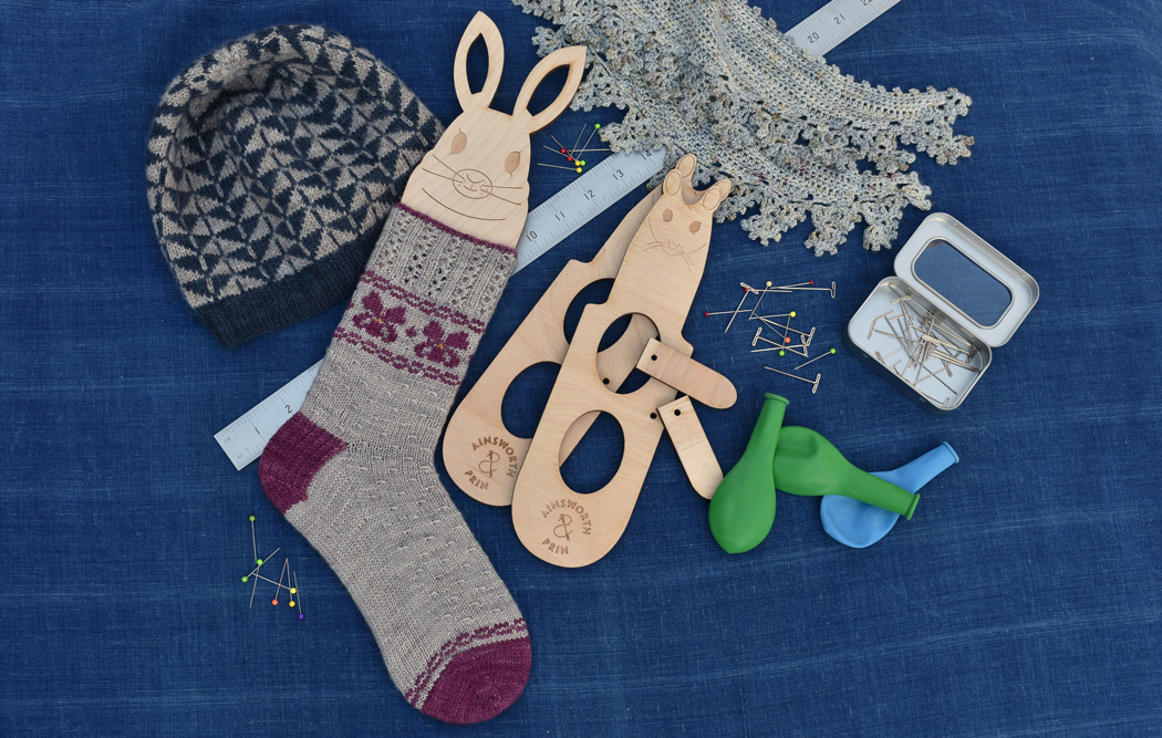 Wooden sock and mitten blockers, ruler, pins, balloons, knitting and crochet on a blue cloth
