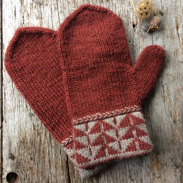 A pair of mittens in a brick red with a geometric colour work cuff laying on a wooden background