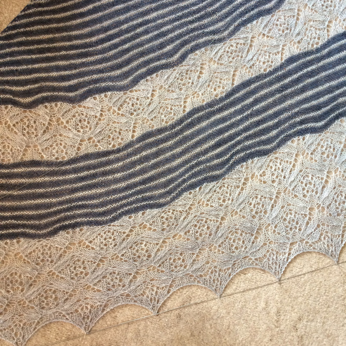 A blue and white knitted shawl with lace inserts. The lace edge is being stretched on wire