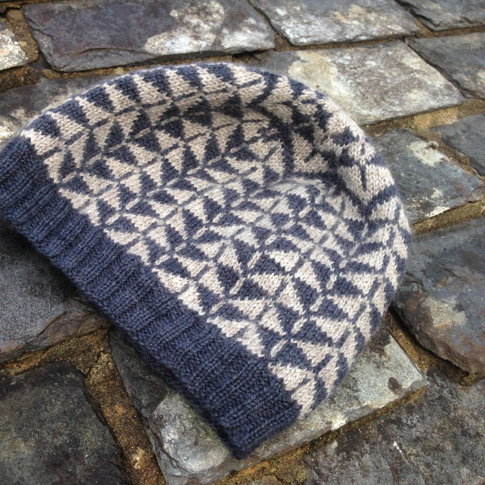 A colour work knitted hat in a geometric design in dark blue and natural on a slate roof