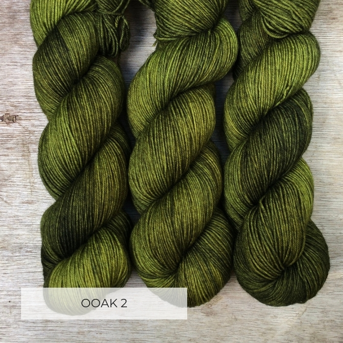 Three skeins of yarn acid green yarn overdyed with moss.