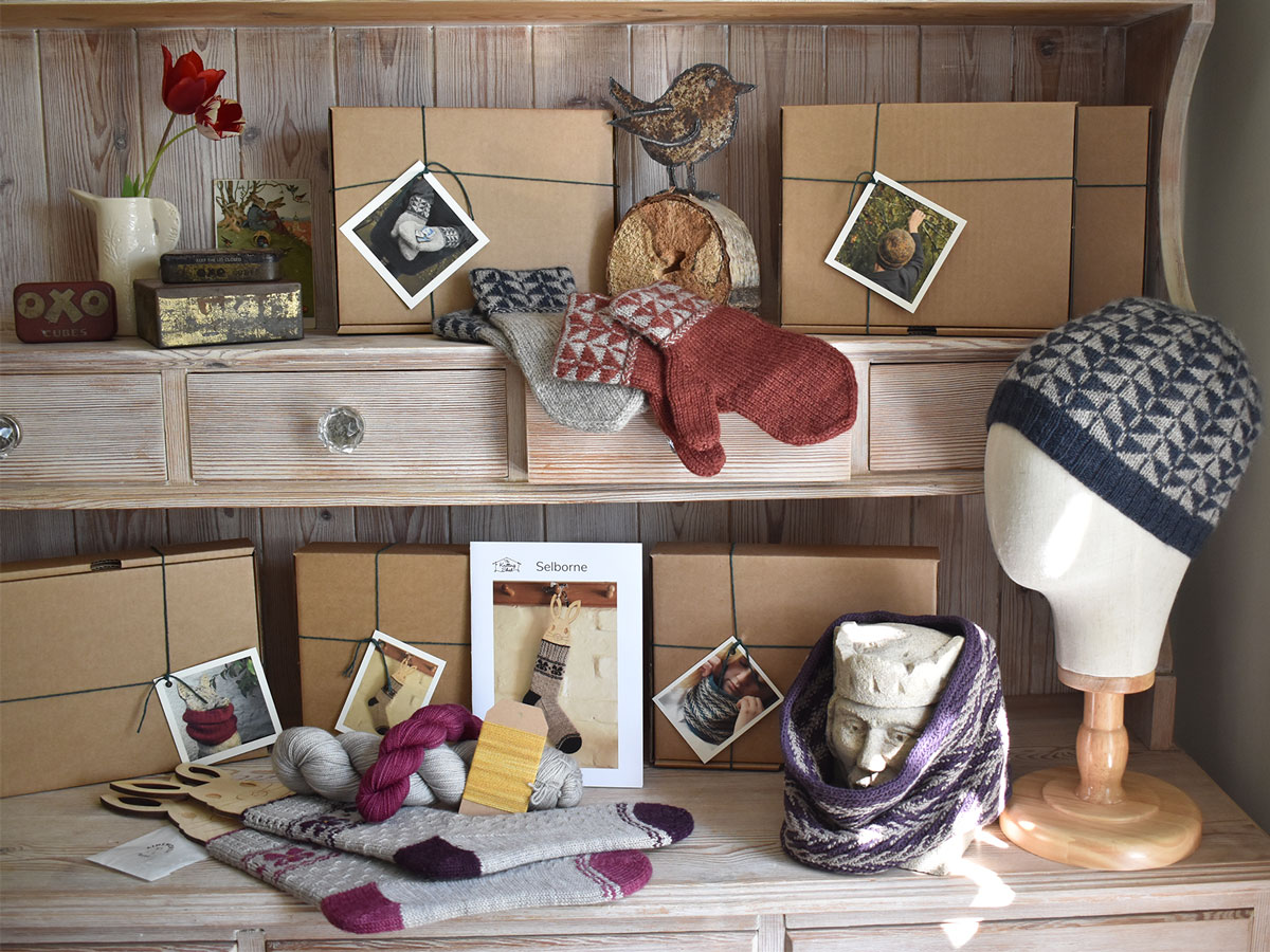 A close up of a kitchen dresser set out with knitting kits in brown boxes and samples
