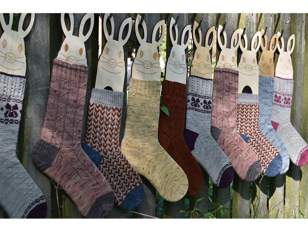 A row of bunny blockers clothed in many different socks all hanging up on a garden fence
