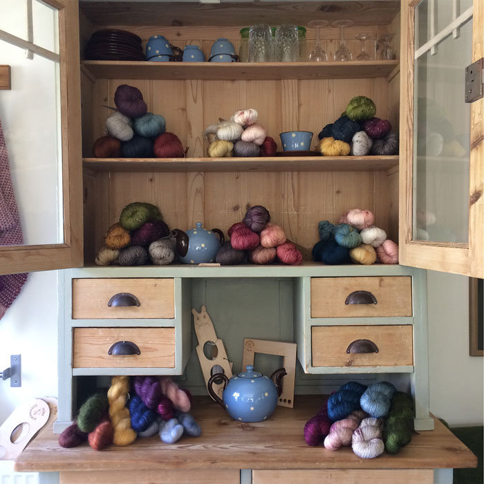 A close up of a kitchen dresser with doors open showing piles of wool