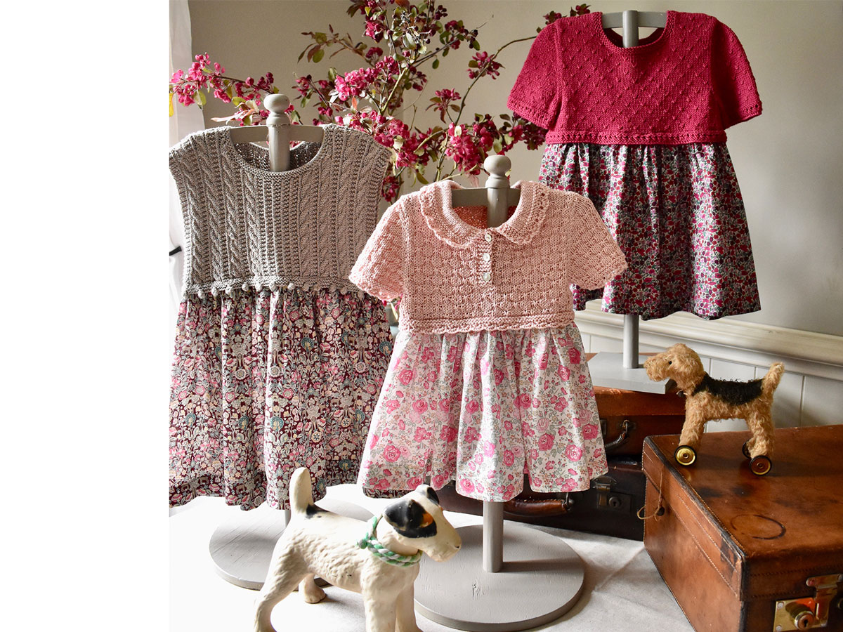 There dresses with knitted tops and floral fabric skirts surrounded by vintage toys and a suitcase