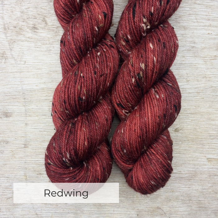 two skeins of hand dyed brick red yarn with black, white and brown neps