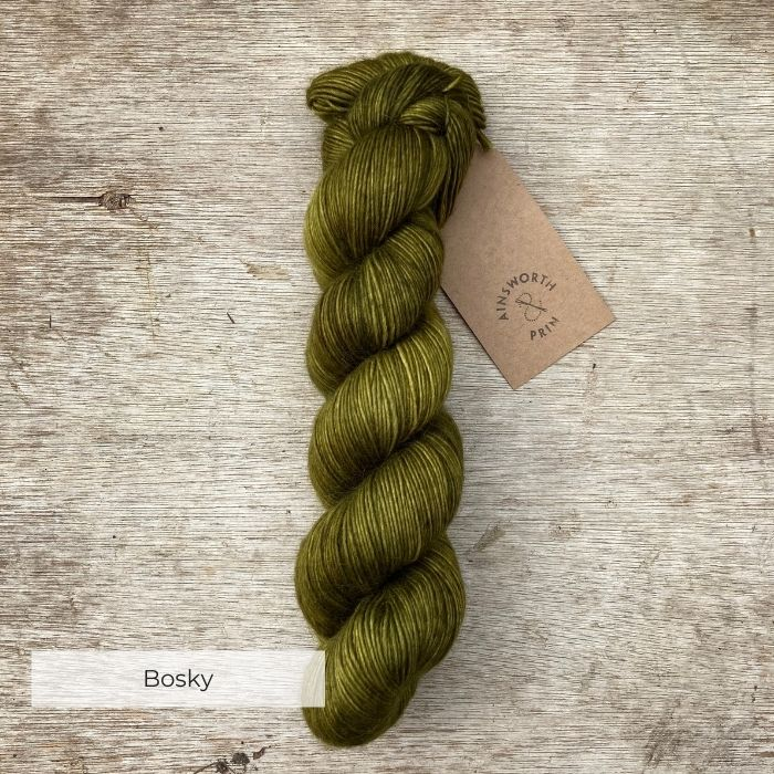 A single skein of deep moss green yarn on a wood background