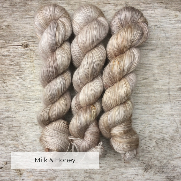 Three skeins of soft and slightly fluffy yarn in cream, gold and light brown