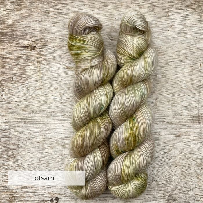 Two skeins of yarn in a neutral stone splashed with moss green