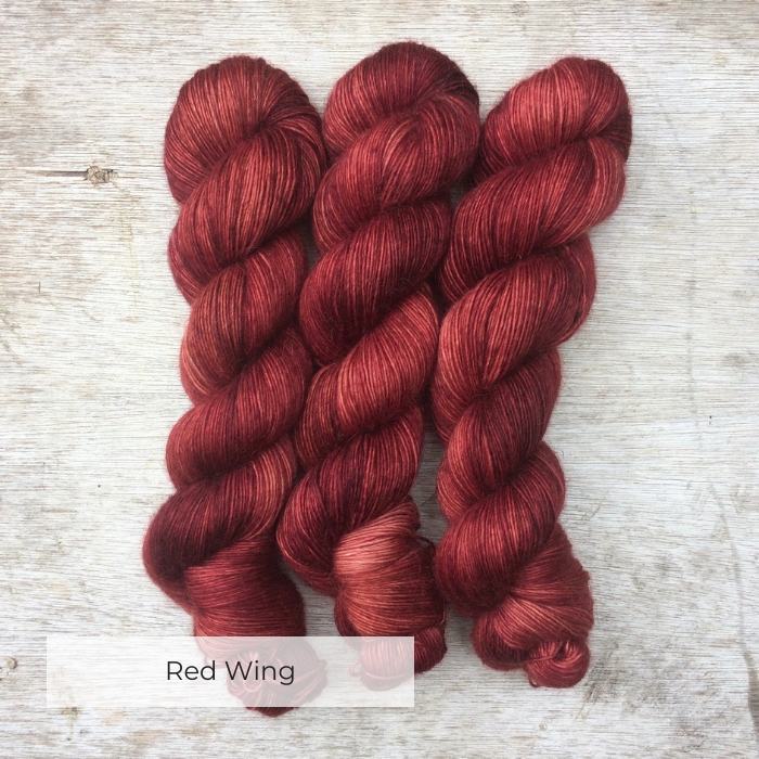 Three skeins of soft and slightly fluffy yarn in deep red