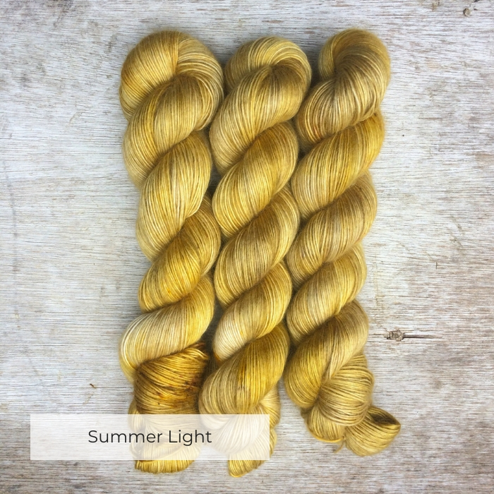 Three skeins of soft, fluffy yarn in shades of yellow with a few yellow and brown speckles