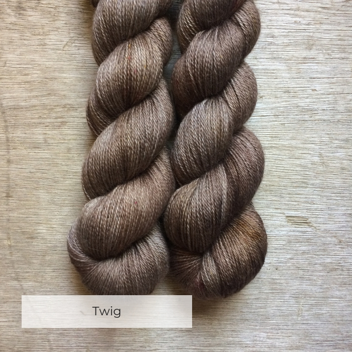 Two skeins of silky alpaca yarn in greys and browns speckled with red and mustard