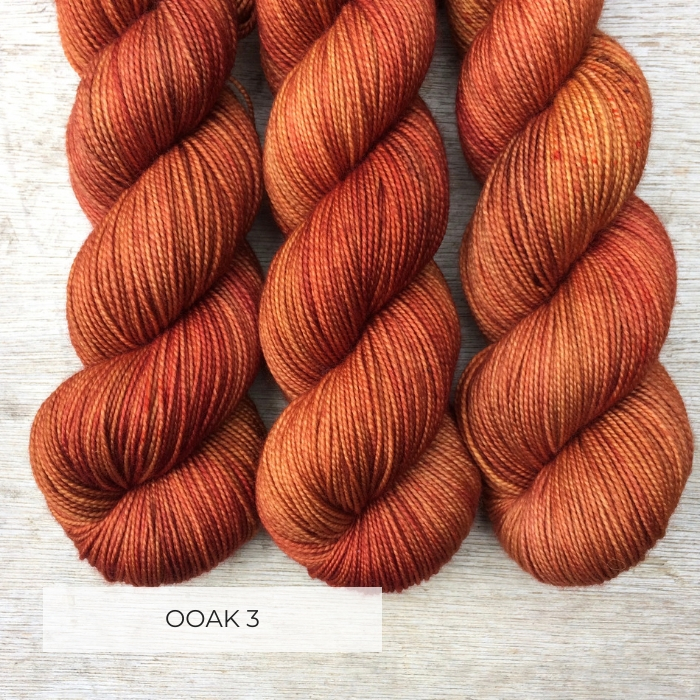Three skeins of yarn the colour of burnt orange