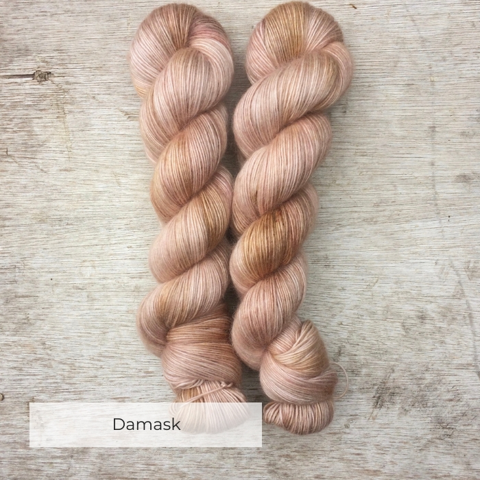 Two skeins of soft and slightly fluffy yarn in shades of very pale terracotta, pink and light brown