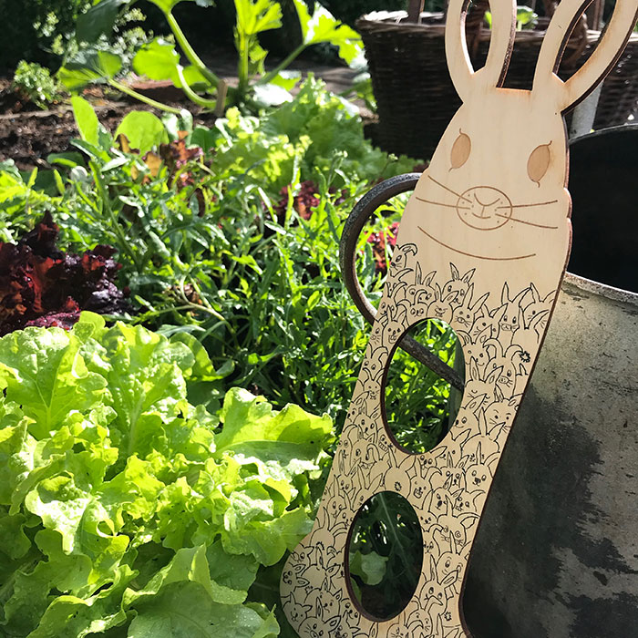 Wooden rabbit shaped sock blocker covered in doodles of rabbits sat in a lettuce patch