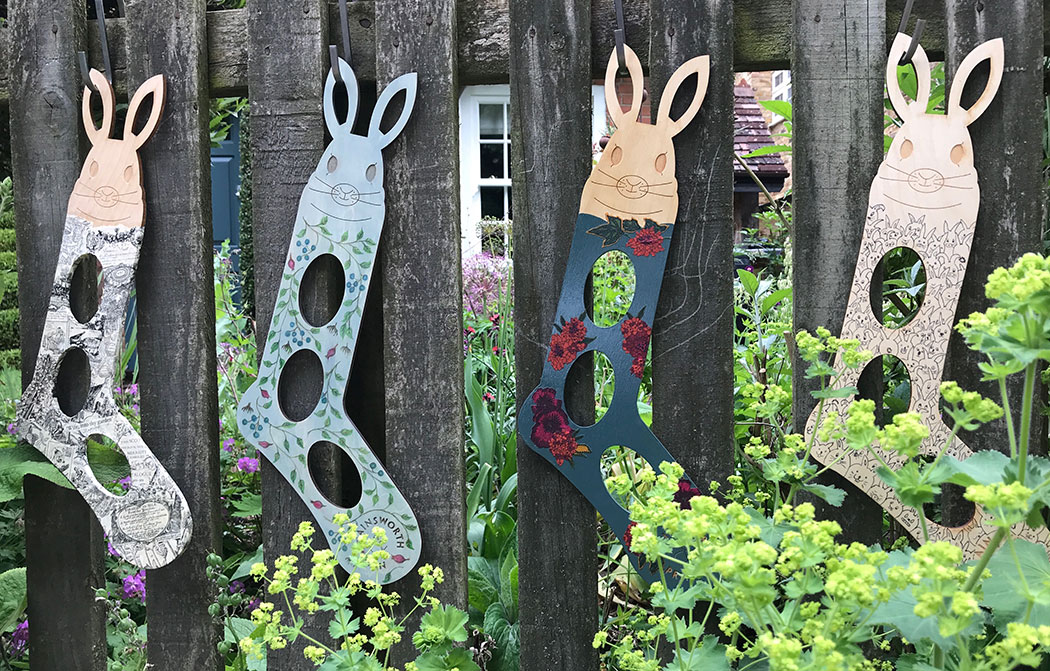 Decorated wooden rabbit shaped sock blockers hanging on a picket fence