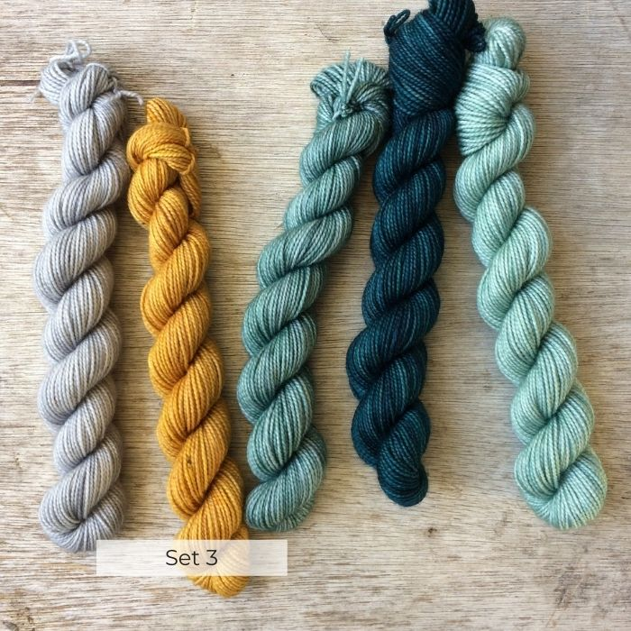 Five little mini skeins of sock yarn thrown down on a wooden background in Teals, grey and yellow