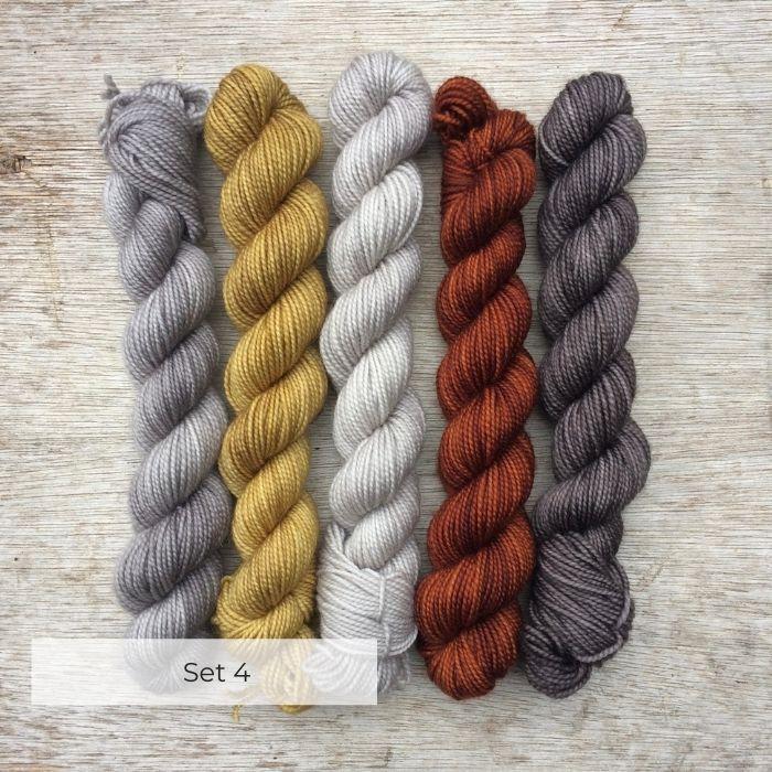 Five mini skeins on a wooden background mid grey, mustard yellow, pale grey, dark rust and dark warm grey