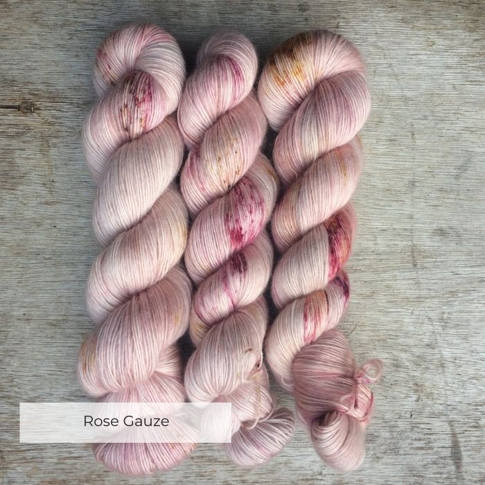 The skeins of fluffy pink yarn speckled in plums and gold