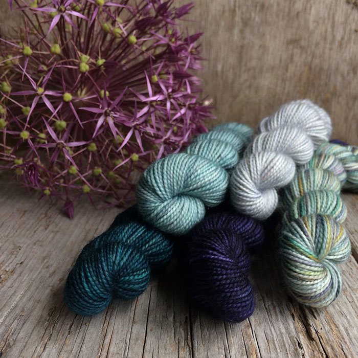 five different coloured mini skeins on a wooden background with a large allium seed head