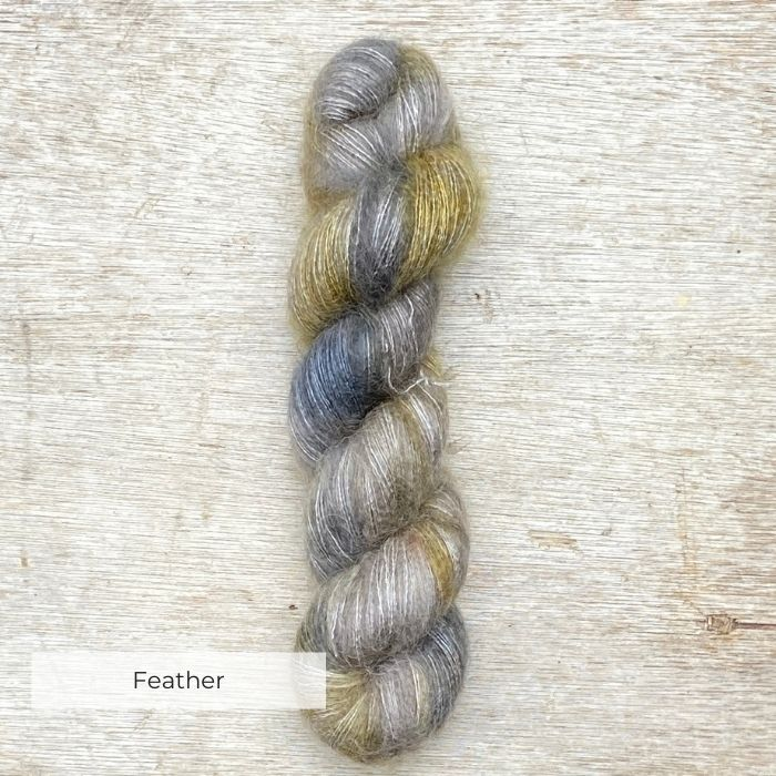 A single skein of fluffy mohair in greys and golds