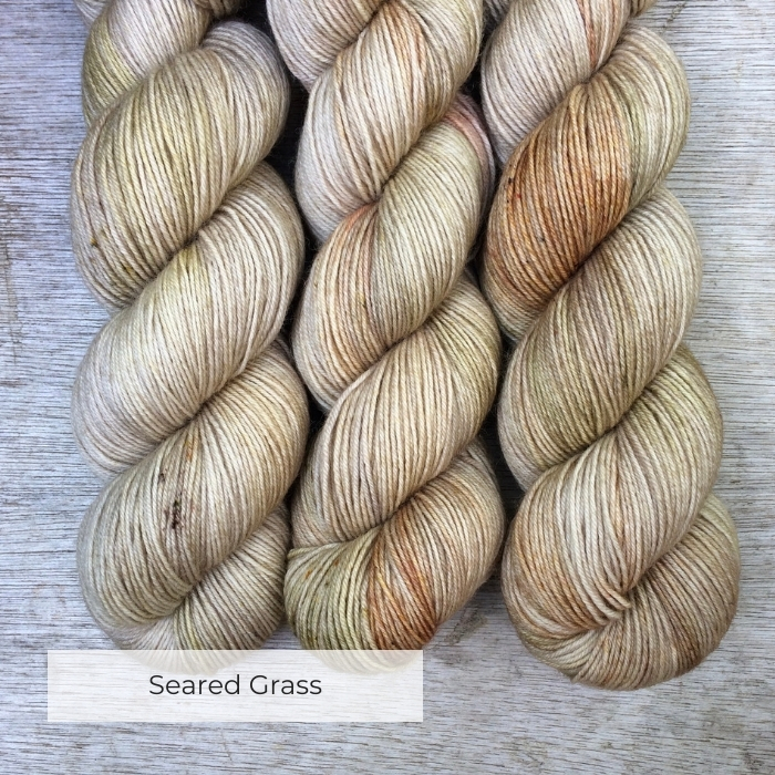 Three skeins of wool splashed with buff, tan and moss green with brown and gold speckles
