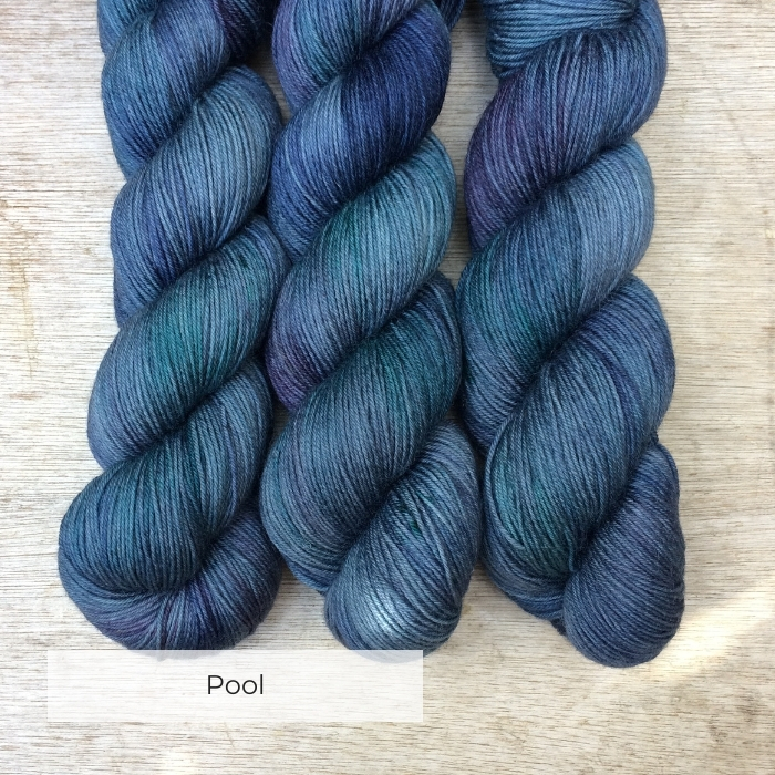 Three skeins of British sock yarn in shades of deep blue, green and purple