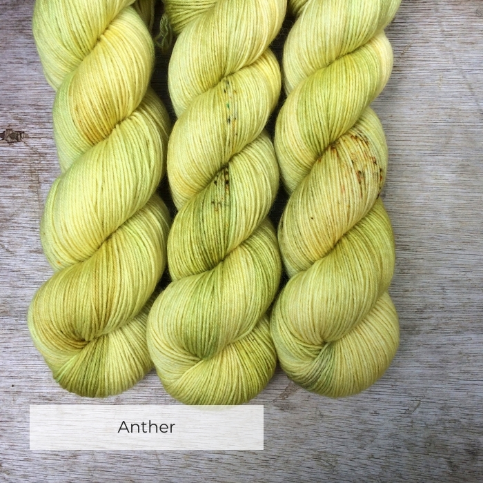 Three skeins of pale yellow and green with speckles of gold and brown