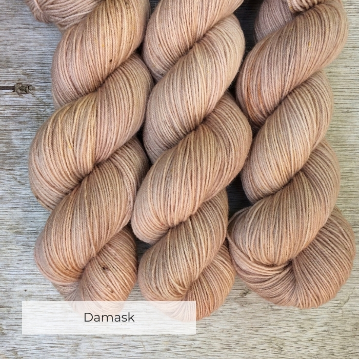 Three skeins of soft yarn the colour of whitewashed terracotta